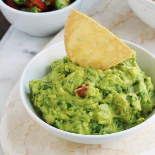Apprenez comment faire le guacamole traditionnel mexicain. Une recette santé express qui accompagne de nombreux plats classiques mexicains. Composé de peu d'ingrédients : avocat, tomate, oignon, coriandre, jus de lime et sel.