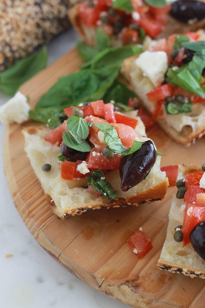 Ces tartines à la salade crétoise sont croustillantes, pleines de saveurs d'été et fraîches. Tranches de pain, tomates, feta, câpres, olives, huile d'olive, herbes fines fraîches.
