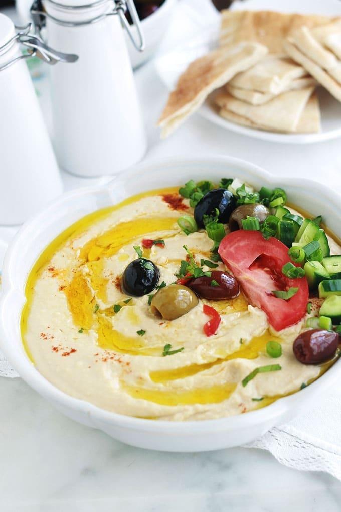 La recette du houmous traditionnel libanais. Une dip santé très populaire : purée de pois chiches à la crème de sésame ou tahini. Peu d'ingrédients : pois chiches, crème de sésame (tahina), ail, jus de citron. Pour servir : de l'huile d'olive et éventuellement des épices, herbes aromatiques et légumes. Il est très facile et rapide. Prêt en moins de 5 minutes!