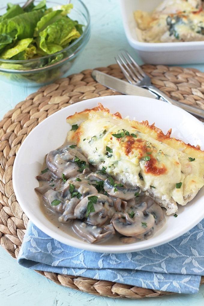 Roulé de poulet farci aux épinards, feta et persillade. Gratiné au four avec du fromage. Accompagné d'une sauce crémeuse aux champignons.