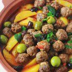 Tajine aux boulettes de viande, pommes de terre et olives. Le tout est cuit dans une sauce tomate. Un plat simple, complet et réconfortant.