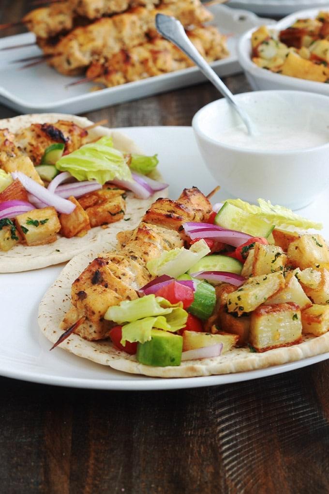 Pain pita au brochettes de poulet mariné à la libanaise (chich taouk), des pommes de terre frites épicées en sauce citronnée à l'ail et coriandre, des crudités et une sauce blanche. Une recette toute simple, facile et délicieuse.