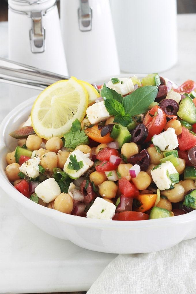 Salade de pois chiches à la grecque rafraîchissante. Une recette facile et rapide (5 minutes!). Des pois chiches, tomates, concombres, oignons, feta, olives kalamata et aromates. Le tout arrosé d'une vinaigrette grecque toute simple. C'est une salade économique, végétarienne et vegan (sans la feta!).
