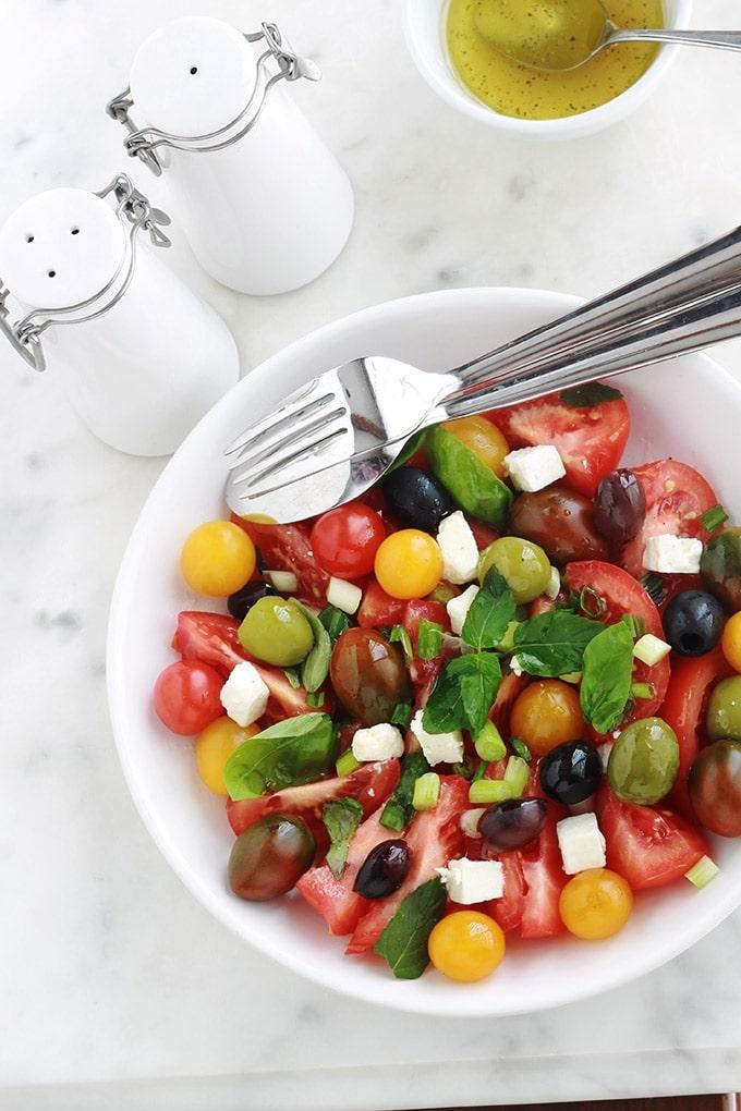 Délicieuse salade de tomates avec du fromage feta, des olives et du basilic. Le tout arrosé d'une vinaigrette toute simple. C'est l'une de mes salades estivales préférées, très parfumée, facile et rapide.