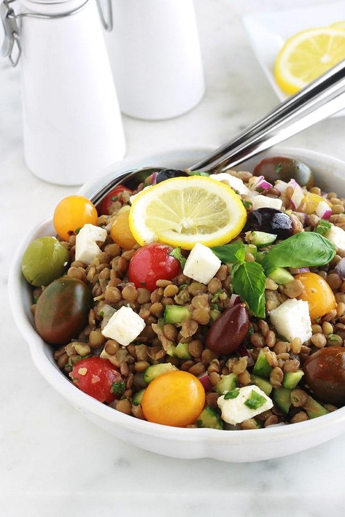 Salade de lentilles à la grecque, facile, très rapide et pleine de saveurs. Composée de lentilles, tomates, feta, concombre, oignons et olives, le tout arrosé d'une vinaigrette citronnée parfumée aux herbes aromatiques.