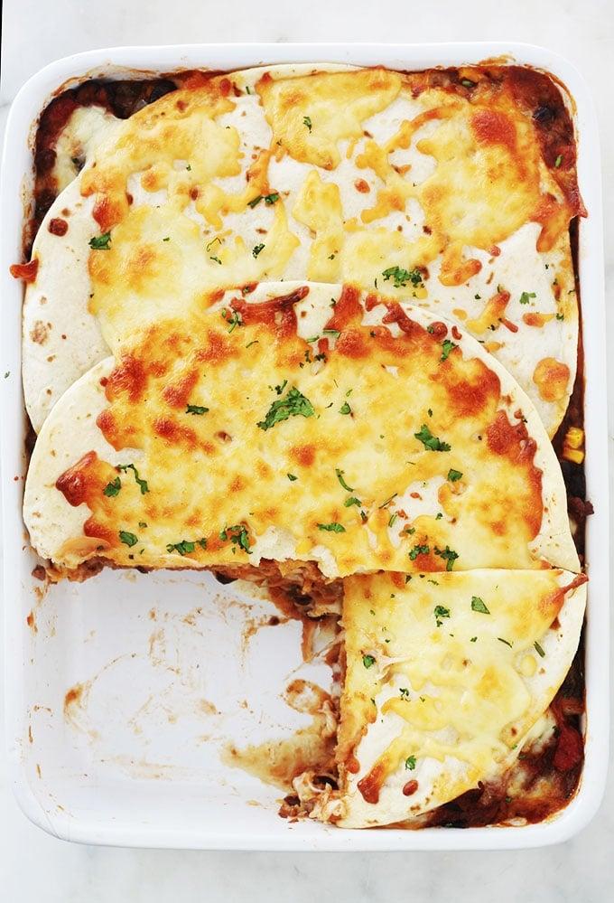 Ces lasagnes à la mexicaine sont très simples à faire et tellement savoureuses. Ce sont des lasagnes revisitées, avec des tortillas (wraps) et du chili con carne rapide (viande hachée, haricots, maïs, poivrons, tomates, assaisonnement), fromage râpé. Sans gluten avec des tortillas à la farine de maïs. Un plat complet et consistant.