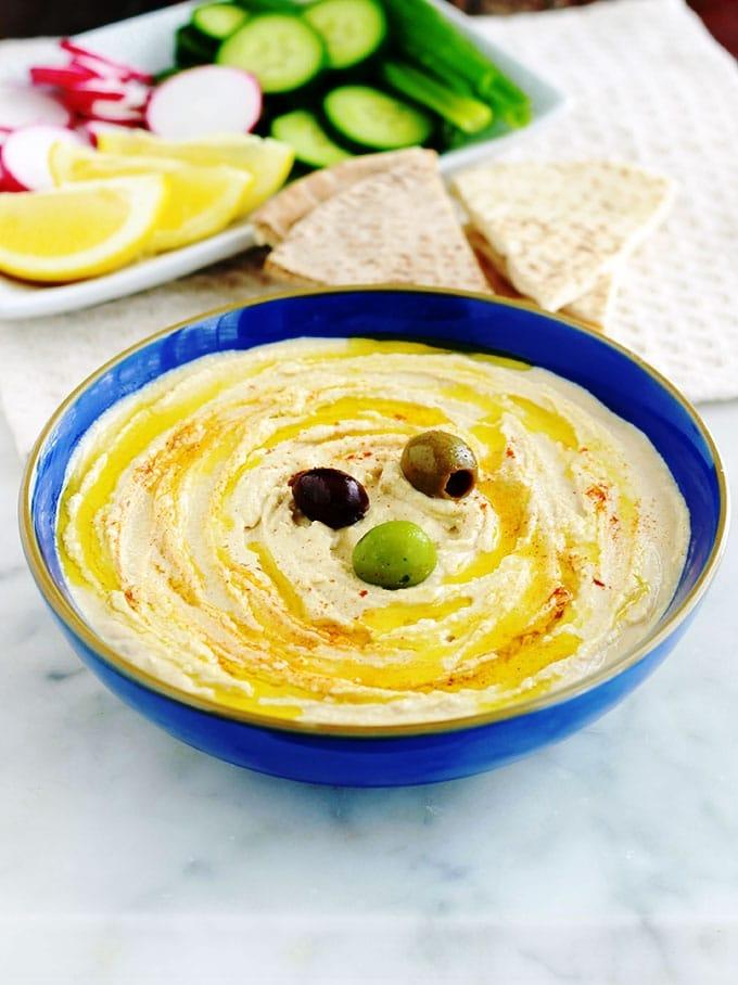 La recette du houmous libanais : une délicieuse purée de pois chiches au tahiné (crème de sésame). Peu d'ingrédients : pois chiches, tahiné, ail, jus de citron. Pour servir : de l'huile d'olive et éventuellement des épices, herbes fines, crudités, pain pita. Le houmous maison est tellement meilleur que celui du commerce, et en plus il est facile et rapide : prêt en moins de 5 minutes!