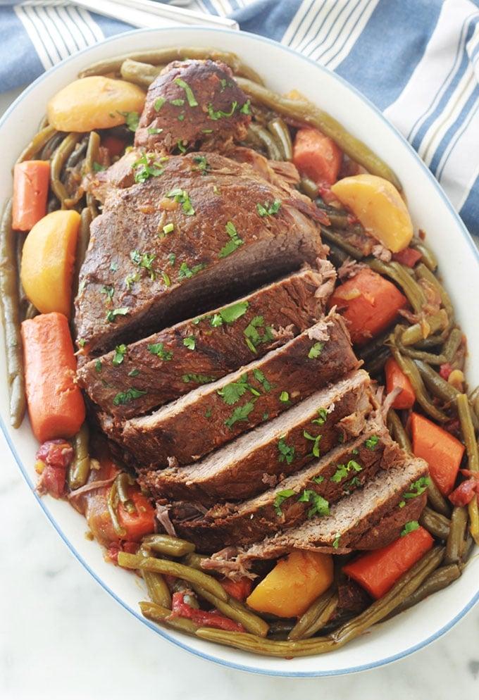 Rôti de boeuf braisé dans une cocotte, très tendre et plein de saveurs. C'est une recette facile et inratable. Un plat complet avec des légumes (haricots verts, pommes de terre, carottes, oignons, tomates). Le rôti est mijoté longuement, à feu doux. En fin de cuisson, la viande est moelleuse et juteuse. Idéal pour le repas de dimanche et pour avoir des restes pour les jours de semaine.