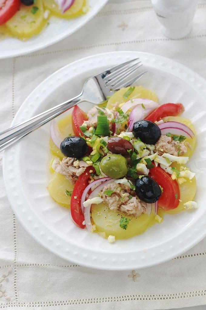 Salade de pommes de terre au thon simplissime avec tomate, oignon et olives. Vinaigrette sans mayonnaise : huile d'olive, jus de citron ou vinaigre, herbes aromatiques, épices. Tellement simple et tellement bonne.