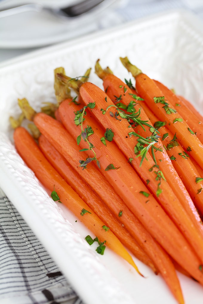 Recette des carottes rôties au miel et aux herbes. Simple et rapide. Les carottes sont tendres et fondantes. Peu d'ingrédients et moins de 4 minutes de préparation. Superbes pour accompagner presque tout : une viande rouge, un poulet rôti, du poisson…