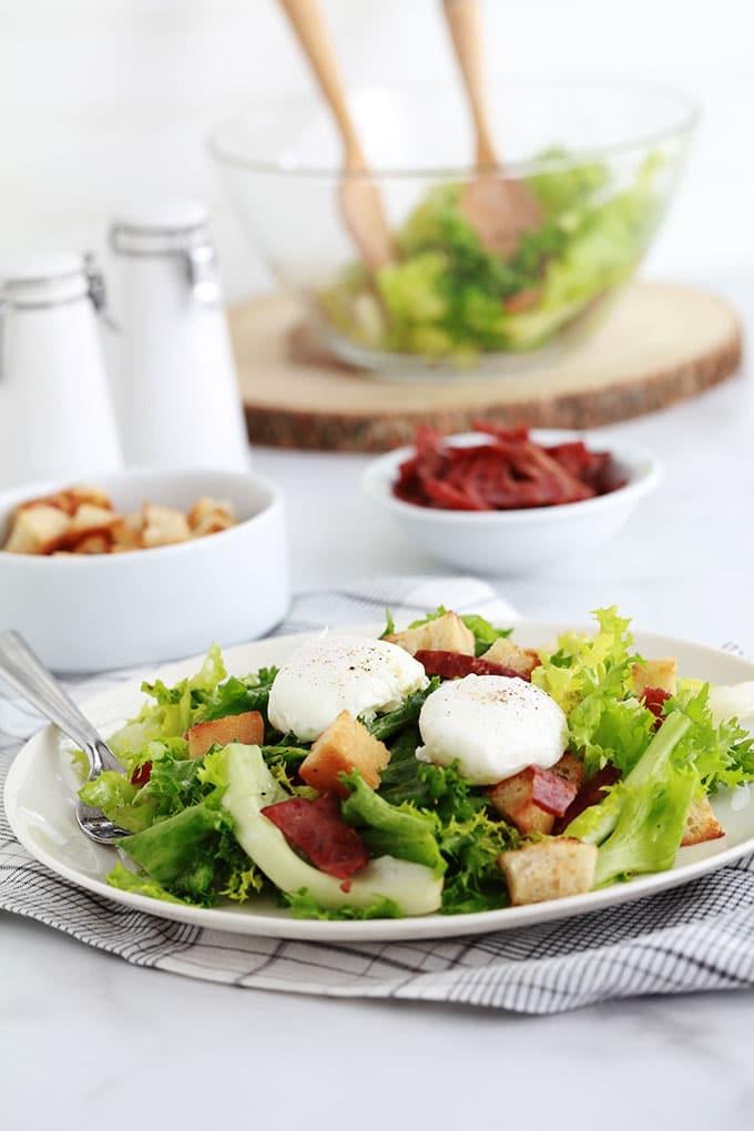 Salade frisée aux oeufs pochés, croûtons croustillants et lardons fumés de dinde. Recette simple et délicieuse. Peut servir de plat principal rapide et léger.
