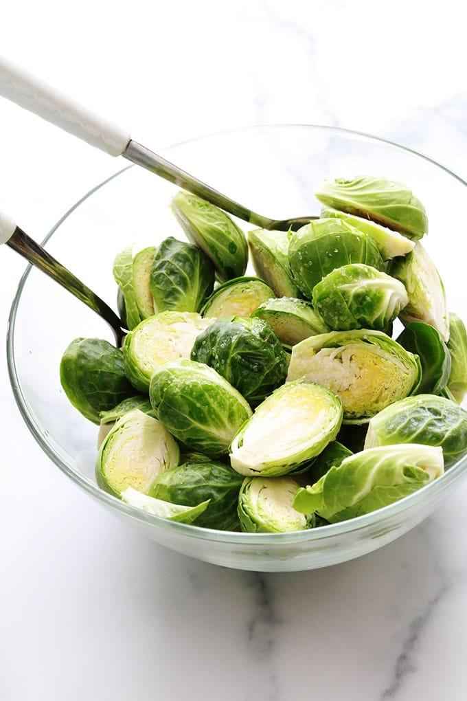 Choux de Bruxelles coupes en deux assaisonnes huile sel dans un bol