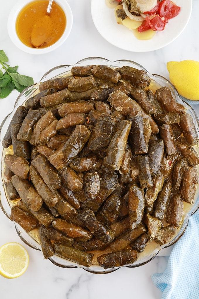 Feuilles de vigne farcies vegetarienne sauce de cuisson et legumes du fond de la cocotte tomate oignon pommes de terre