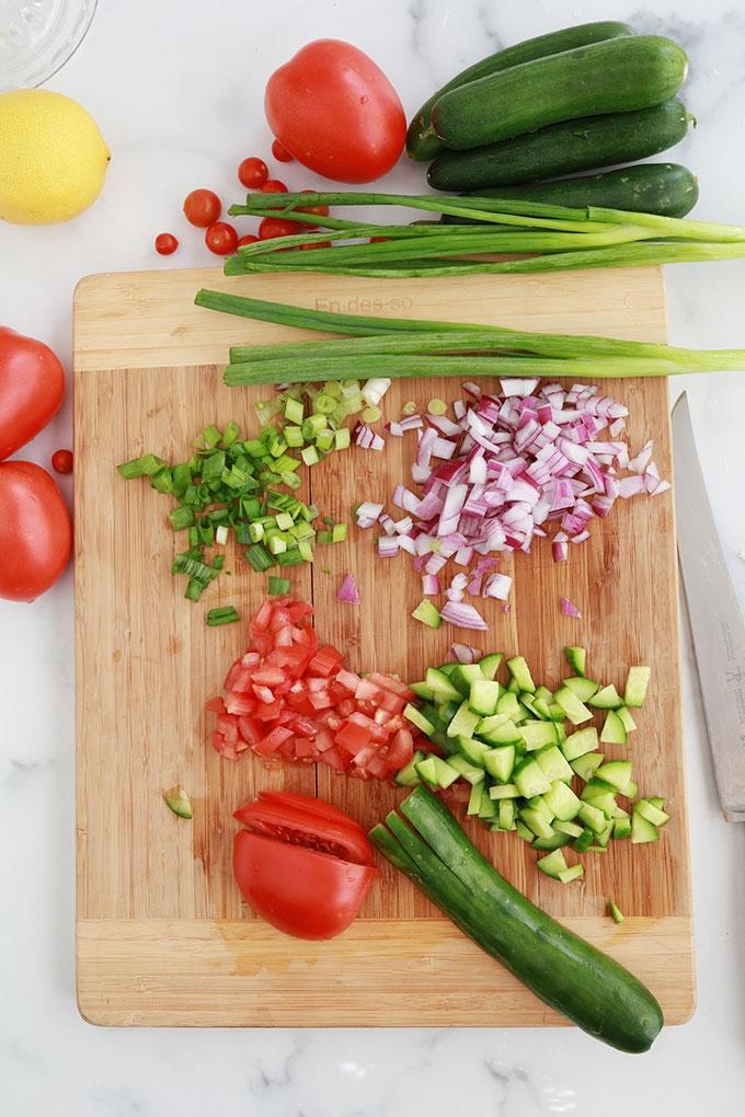 Couper les legumes en petits morceaux - concombre tomates oignon rouge oignons verts