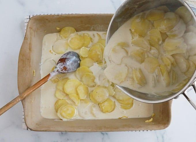Verser rondelles de pommes de terre precuites creme lait dans le plat a gratin