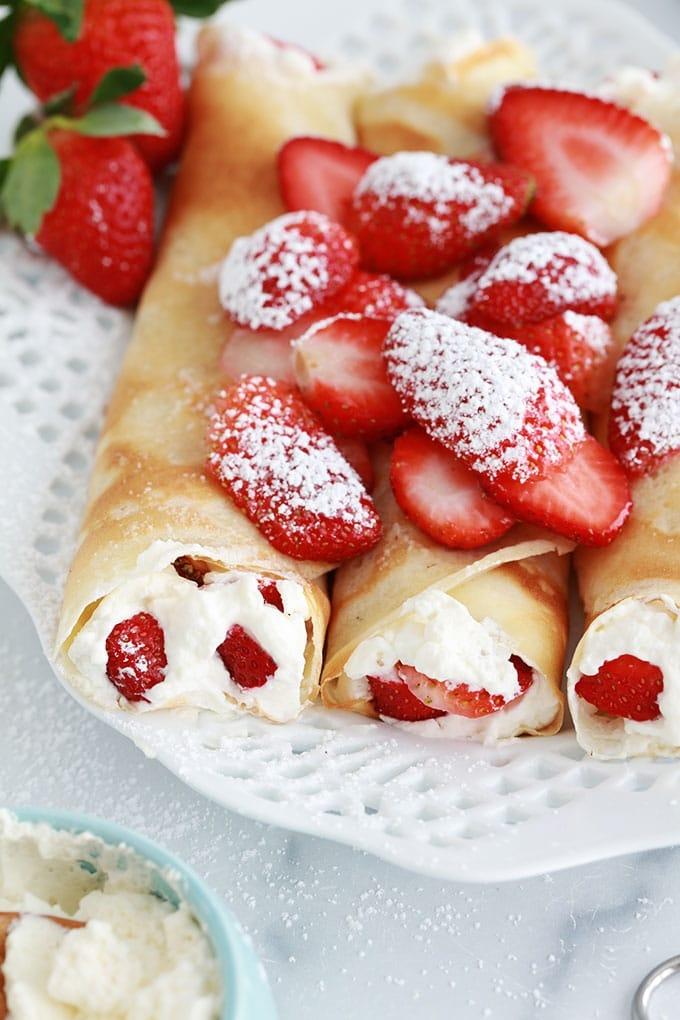 Crepes fourrees de fraises et creme chantilly dans un plat de service