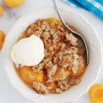 Crumble aux abricots et flocons d'avoine dans un bol avec une boule de glace à la vanille