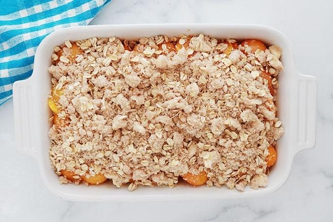 Pate a crumble aux flocons d avoine sur garniture aux abricots dans un plat a gratin avant cuisson