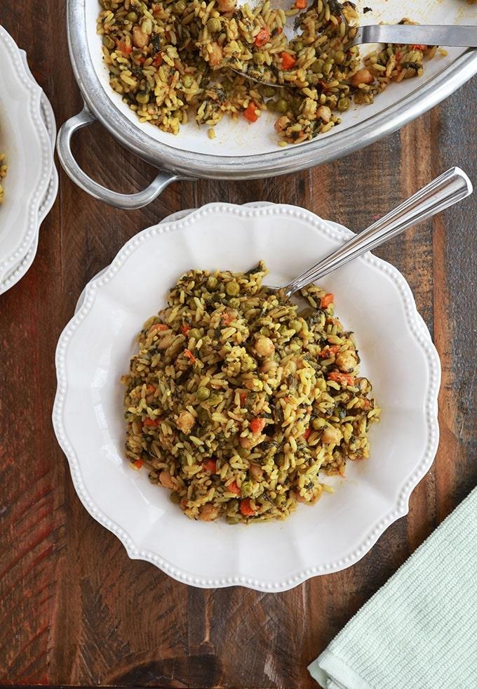 Riz aux légumes cuits à la vapeur servi dans une assiette (pois chiches, épinards, petits pois, carottes, oignons, ail, épices, huile d'olive)
