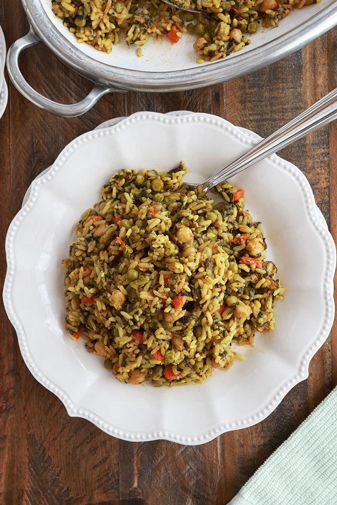Riz vapeur aux légumes servi dans une assiette (pois chiches, épinards, petits pois, carottes, oignons, ail, épices, huile d'olive)